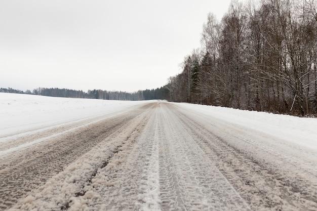 Vestígios deixados de carro na estrada coberta de neve no inverno. foto closeup em tempo nublado. a estrada passa pela floresta com árvores