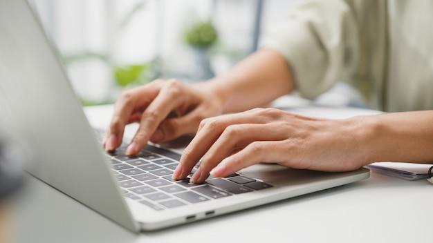 Vestuário casual de jovem empresária freelance usando laptop, trabalhando na sala de estar em casa.
