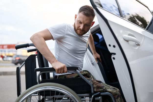 Veterano aposentado é transferido do carro para a cadeira de rodas