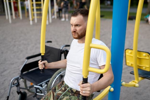 Veterano com deficiência, treinamento esportivo no parque. pessoas paralisadas e dificuldades com deficiências, superação de deficiências. pessoa do sexo masculino com deficiência em campo esportivo