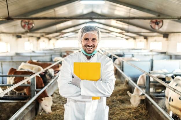 Veterinário caucasiano com a barba por fazer e sorridente, de uniforme, com luvas e rede para o cabelo em pé com a pasta nas mãos no estábulo