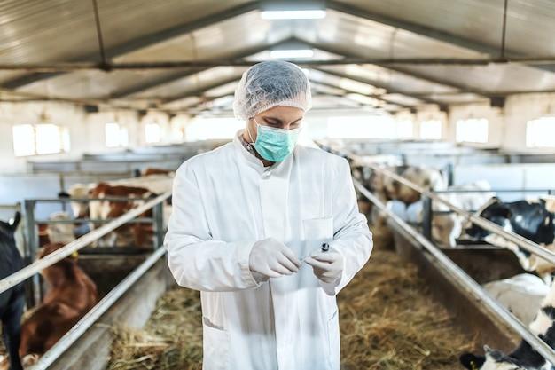 Veterinário caucasiano com uniforme de proteção em pé