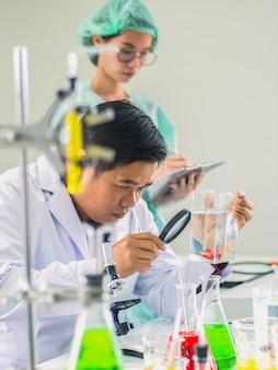 Veterinário, cientista ou pesquisador usando lupa para diagnosticar peixe betta