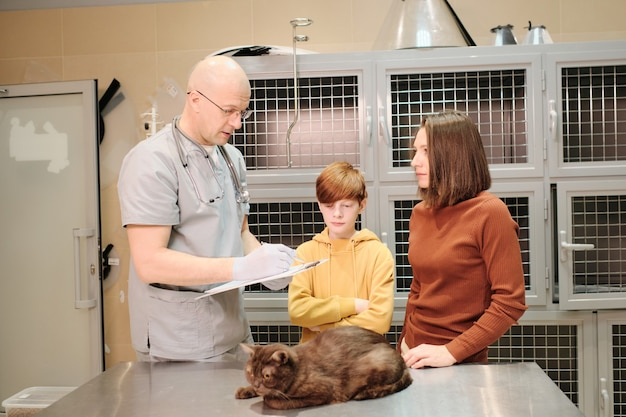 Veterinário dando uma receita de gato para seus donos enquanto eles estão no hospital