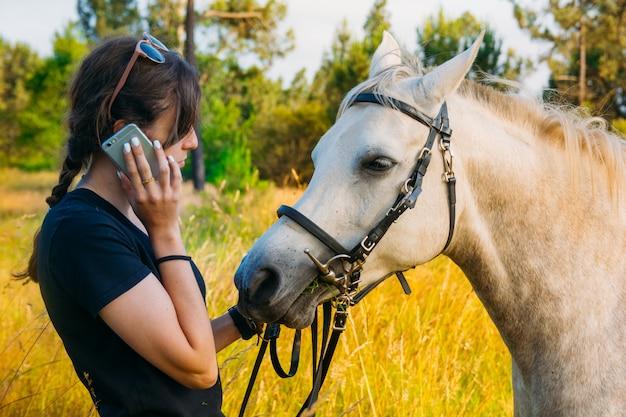 Veterinário feminino ao telefone em pé a cavalo na zona rural