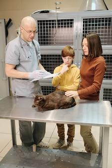 Veterinário maduro de uniforme prescrevendo um remédio para gatos e conversando com seu dono na clínica veterinária