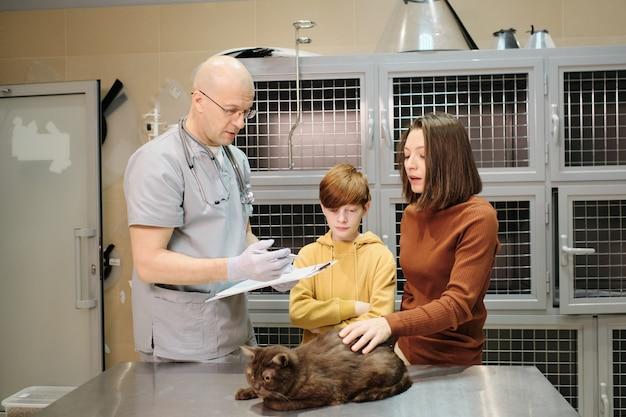 Veterinário maduro uniformizado, tratando de animais domésticos na clínica veterinária, explicando os métodos de tratamento às mulheres