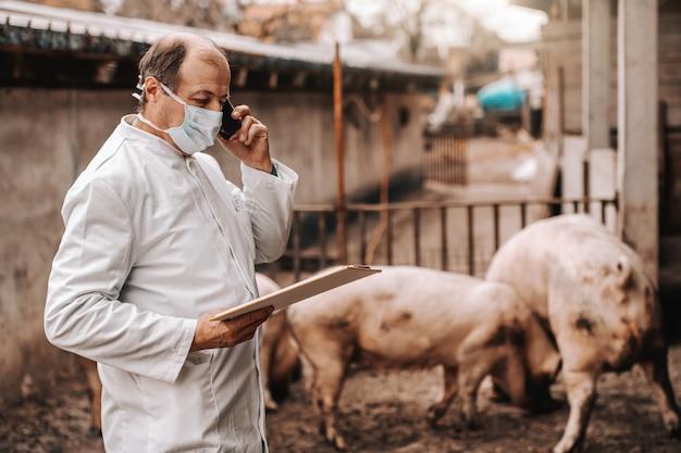 Veterinário sênior no jaleco branco e máscara protetora em olhar para a área de transferência e usando o telefone inteligente em pé na costa.