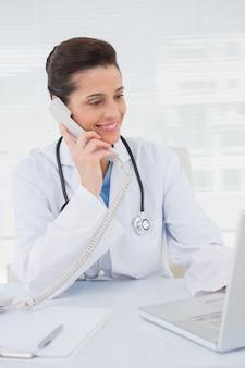 Veterinário telefonando e usando o laptop