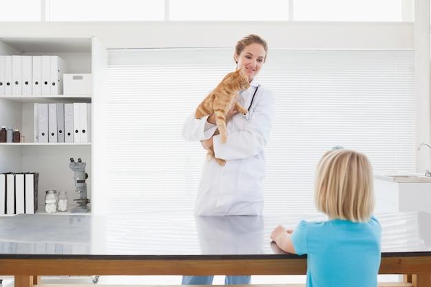 Vetor segurando um gato jovem
