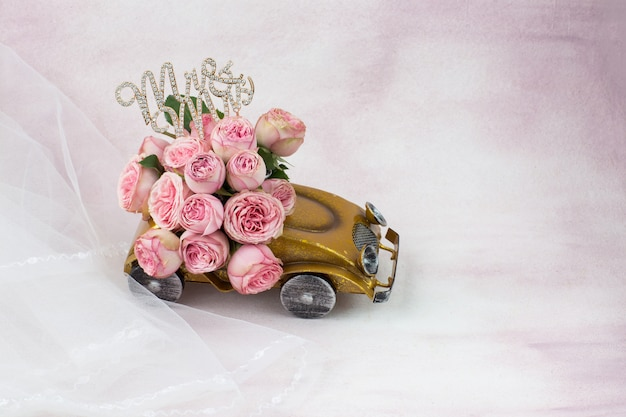 Véu, a inscrição sr. e sra. e um buquê de rosas no carro