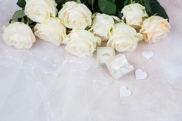 Véu, anel, corações de cetim brancos e um buquê de rosas brancas