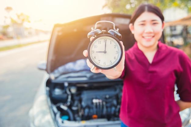 Vezes ao conceito de seleção de carro: mulheres asiáticas segurando o relógio com fundo de capô aberto de carro