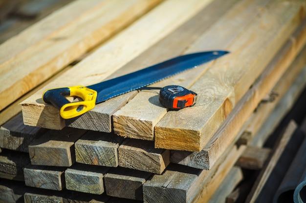 Vi com uma fita métrica de construção em tábuas de madeira. serra. fita de construção. tábuas de madeira