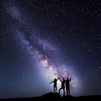 Via láctea. céu noturno com estrelas e a silhueta de uma família feliz na montanha com os braços erguidos.