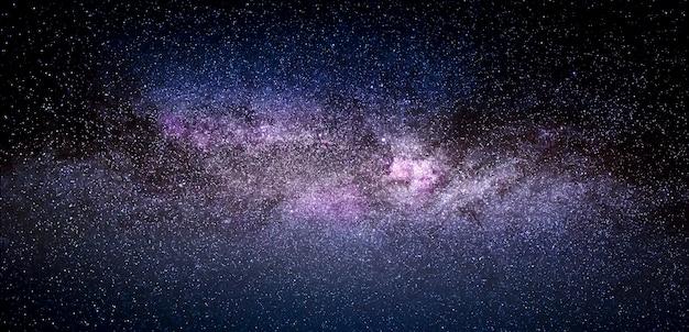Via láctea colorida. paisagem brilhante do céu estrelado de verão à noite. o infinito azul do espaço e brilhantes aglomerados de estrelas na manga da galáxia.