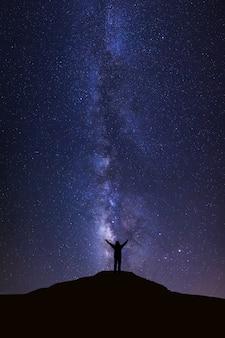 Via láctea com estrelas e silhueta do homem que está na alta montanha