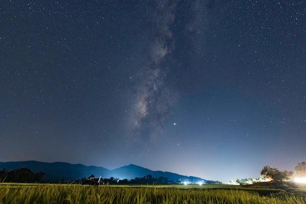 Via láctea com marte na noite escura sobre os campos verdes de arroz e a luz da vila rural de arroz