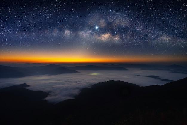 Via láctea e estrela sobre montanhas.