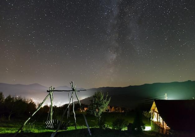 Via láctea no céu da noite estrelada e quintal rural iluminado na cor verde na colina da montanha.