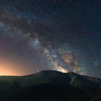 Via láctea sobre uma paisagem de noite nas montanhas da espanha