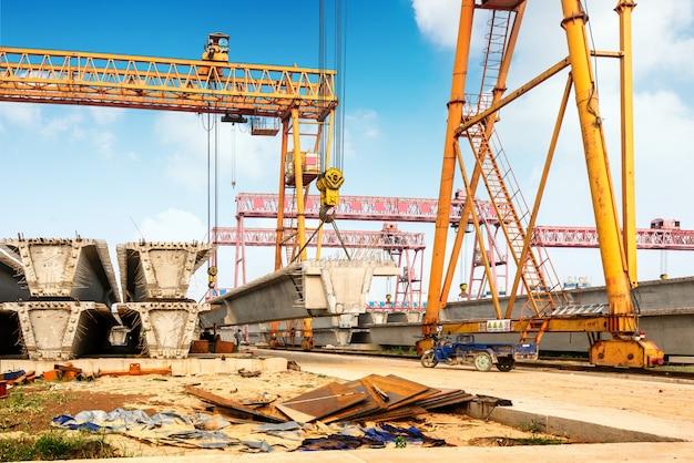 Viaduto de construção, guindastes e trabalhadores ocupados.