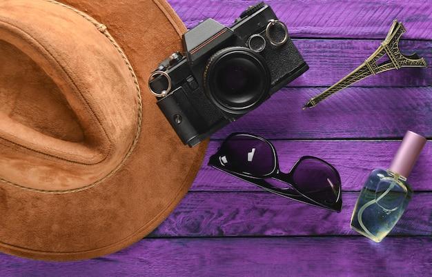 Viagem à frança, paris. chapéu de feltro, câmera de filme, óculos de sol, frasco de perfume, estátua de lembrança do layout da torre eiffel em uma mesa de madeira colorida. paixão por viagens, conceito de desejo por viajar. postura plana.