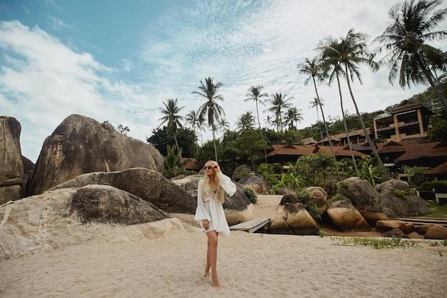 Viagem a uma ilha tropical da jovem modelo posando na praia com um exótico resort de luxo.