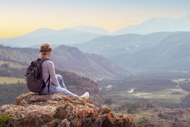Viagem, alpinista de mulher com mochila relaxante durante a caminhada no topo da montanha ao pôr do sol.