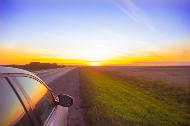 Viagem ao pôr do sol. a trilha entra em um pôr do sol laranja. o carro está na beira da estrada