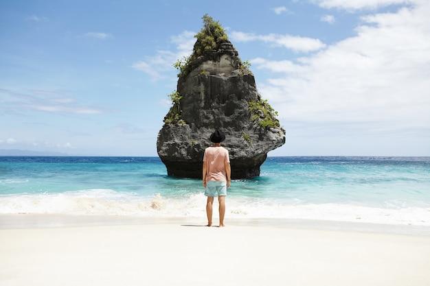 Viagem, aventura e turismo. homem descalço na moda vestindo shorts, camiseta e chapéu, meditando à beira-mar, em frente à ilha de pedra. turista caucasiana elegante admirando a bela vista