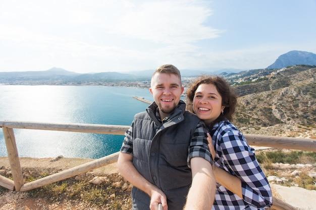 Viagem de férias e conceito de férias casal feliz tirando selfie sobre uma bela paisagem