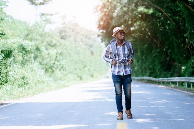 Viagem de homem africano carregando mochila andando na estrada rodovia