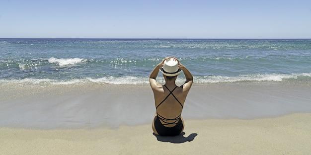 Viagem de luxo para a sardenha. mulher com chapéu na praia em villasimius
