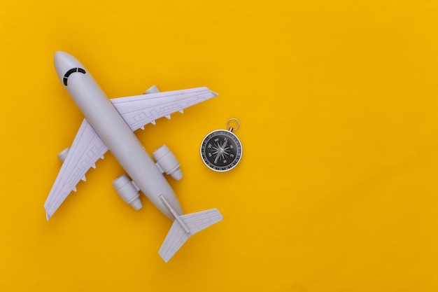 Viagem de minimalismo, aventura plana lay. bússola e avião em fundo amarelo. copie o espaço. vista do topo