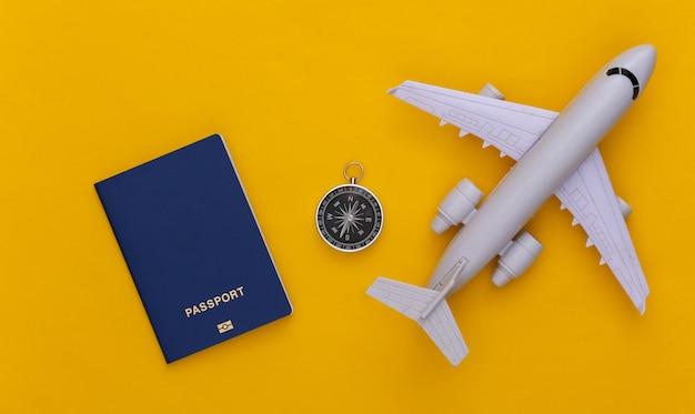 Viagem de minimalismo, aventura plana lay. bússola e avião, passaporte em fundo amarelo. vista do topo