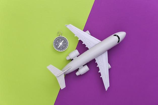 Viagem de minimalismo, aventura plana lay. bússola e avião sobre fundo verde roxo. vista do topo