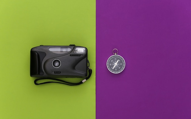 Viagem de minimalismo, aventura plana lay. bússola e câmera no fundo verde roxo. vista do topo