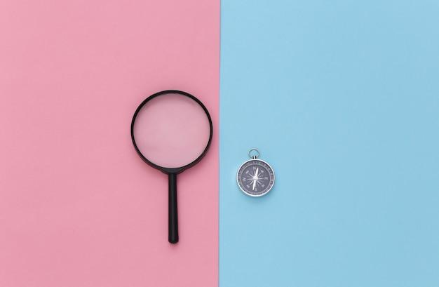 Viagem de minimalismo, aventura plana lay. bússola e lente de aumento em um fundo azul-rosa pastel. vista do topo