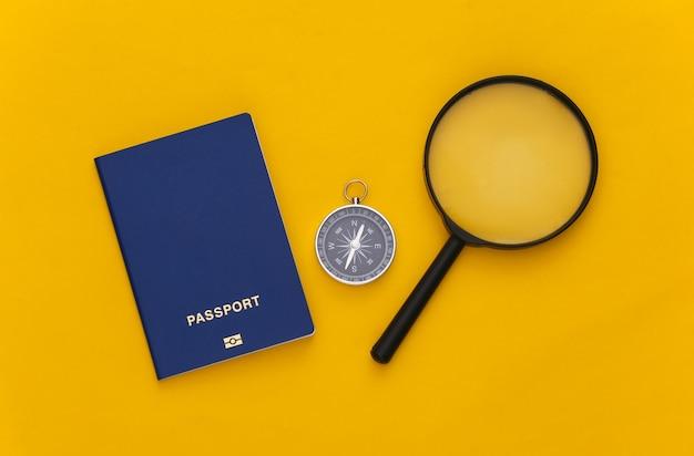 Viagem de minimalismo, aventura plana lay. bússola e lupa, passaporte em fundo amarelo. vista do topo