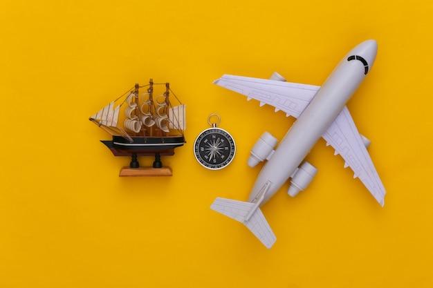 Viagem de minimalismo, aventura plana lay. bússola e navio, avião de ar em fundo amarelo. vista do topo