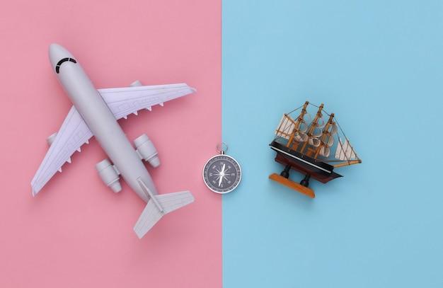 Viagem de minimalismo, aventura plana lay. bússola e navio, avião de ar em fundo azul-rosa pastel. vista do topo