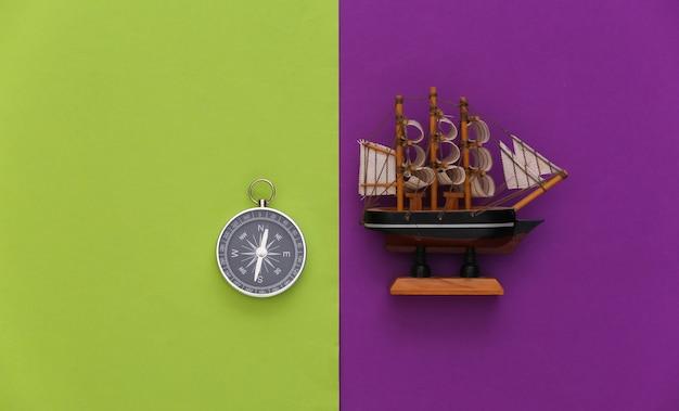 Viagem de minimalismo, aventura plana lay. bússola e navio em fundo verde roxo. vista do topo