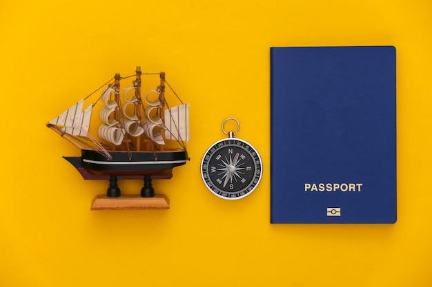 Viagem de minimalismo, aventura plana lay. bússola e navio, passaporte em fundo amarelo. vista do topo
