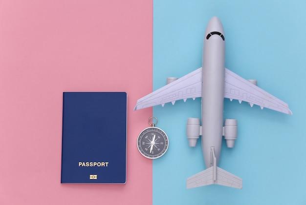 Viagem de minimalismo, aventura plana lay. bússola e passaporte, avião em fundo azul-rosa pastel. vista do topo