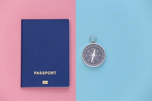 Viagem de minimalismo, aventura plana lay. bússola e passaporte em um fundo azul-rosa pastel. vista do topo