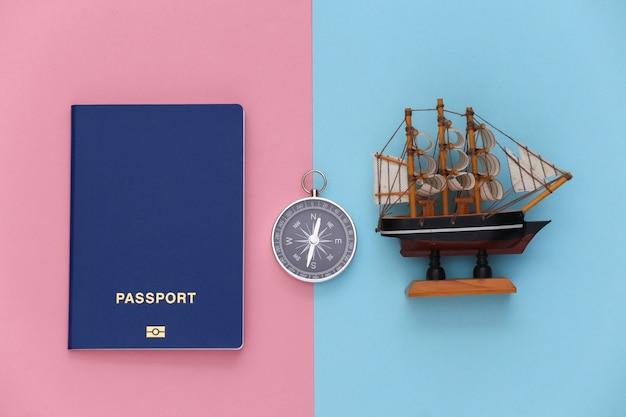 Viagem de minimalismo, aventura plana lay. bússola e passaporte, enviar em um fundo azul-rosa pastel. vista do topo