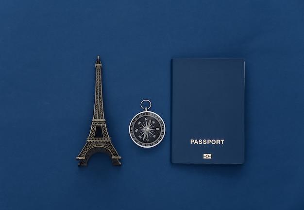 Viagem de minimalismo, aventura plana lay. bússola, passaporte e estatueta da torre eiffel em fundo azul clássico. vista do topo