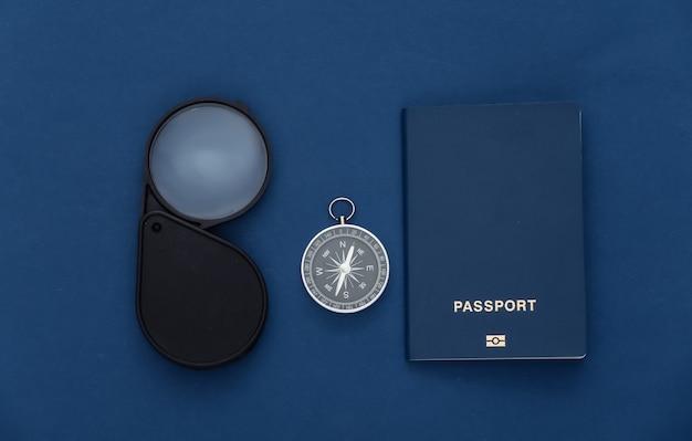 Viagem de minimalismo, aventura plana lay. bússola, passaporte e lupa no fundo azul clássico. vista do topo
