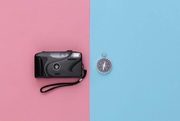 Viagem de minimalismo, aventura plana lay. câmera e bússola em fundo azul-rosa pastel. vista do topo